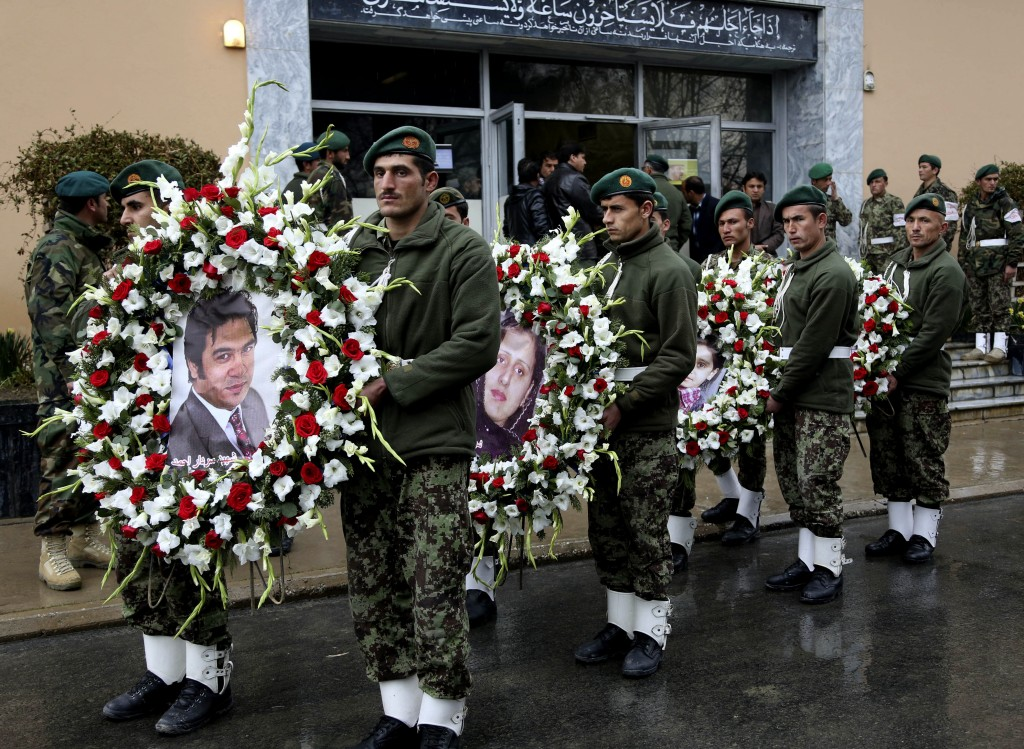 Afghan guards of honor carry wreaths with photographs of Agence France-Presse journalist Sardar Ahmad, his wife Humaira and their children Nilofar and Omar in Kabul, Afghanistan, Sunday, March 23. Photo credit: AP Photo/Rahmat Gul