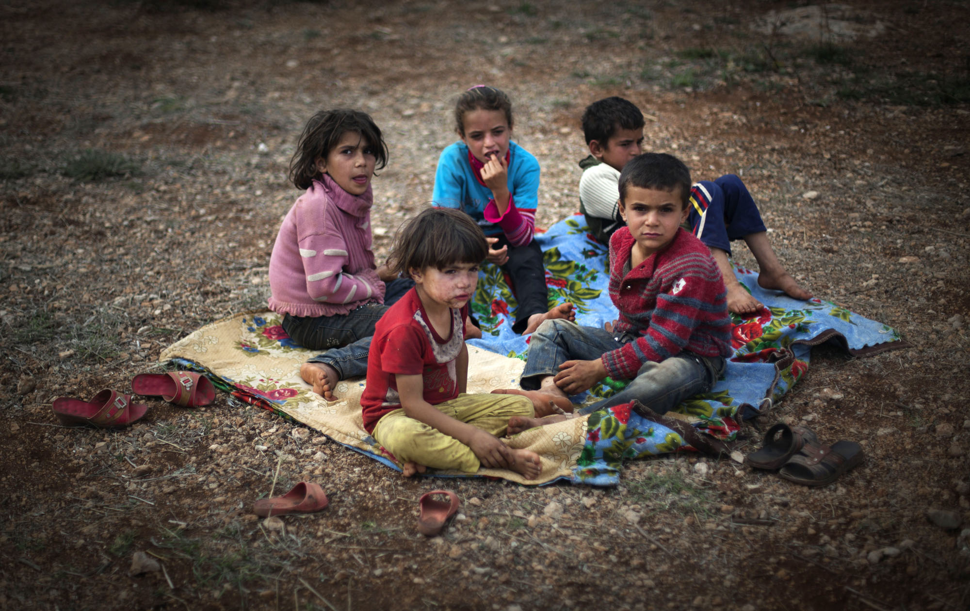 Syrian children who fled with their families from the violence in their village, sit on the ground at a displaced camp in the Syrian village of Atmeh, near the Turkish border with Syria, Thursday, Nov. 8, 2012.(AP Photo/Khalil Hamra)