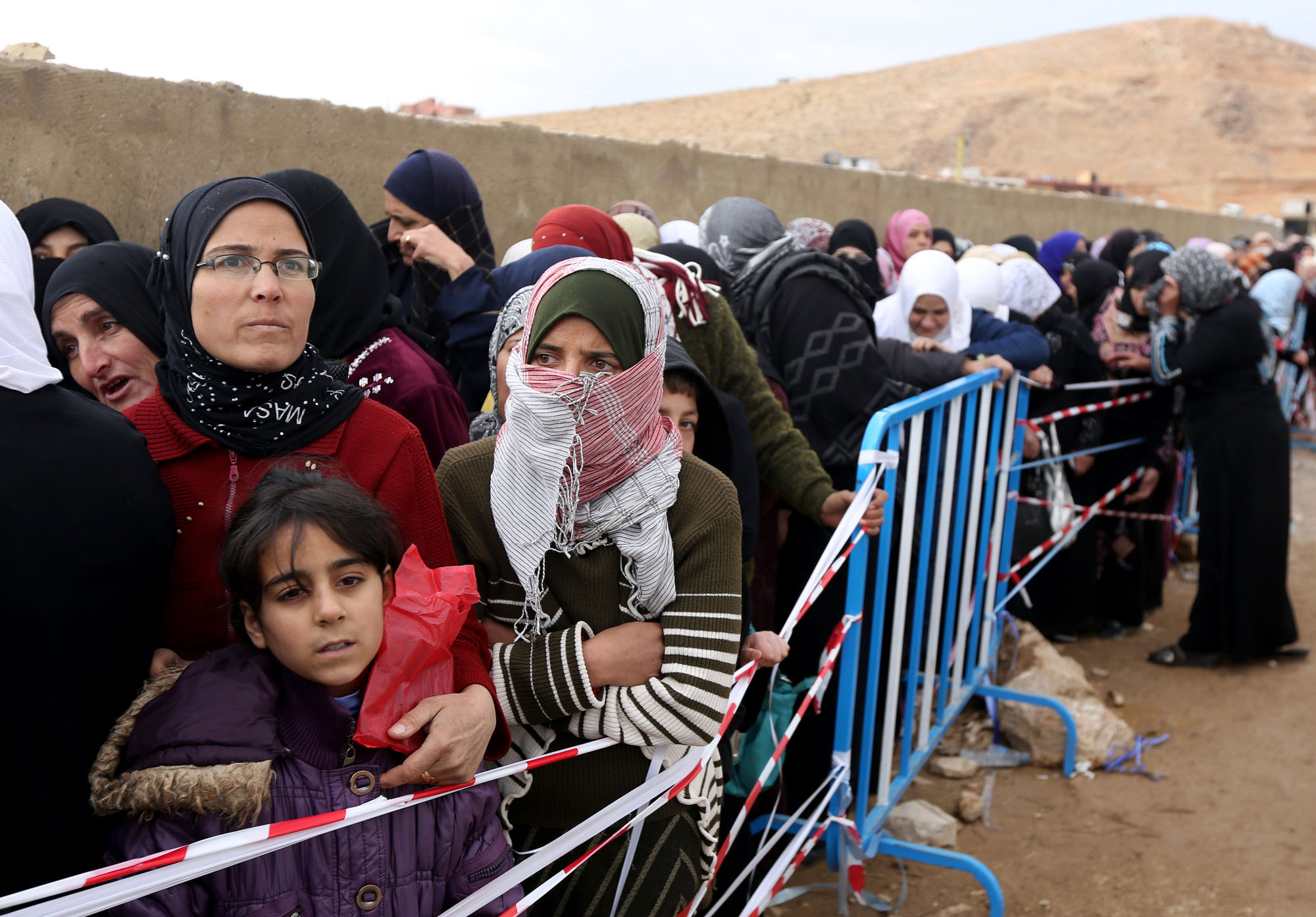 Syrian women stand in line waiting to collect aid from relief agencies helping refugees who fled into the eastern Lebanese border town of Arsal, Lebanon, Monday, Nov. 18, 2013. Thousands of Syrians have fled to Lebanon over the past days as government forces attack the western town of Qarah near the border with Lebanon. (AP Photo/Bilal Hussein)
