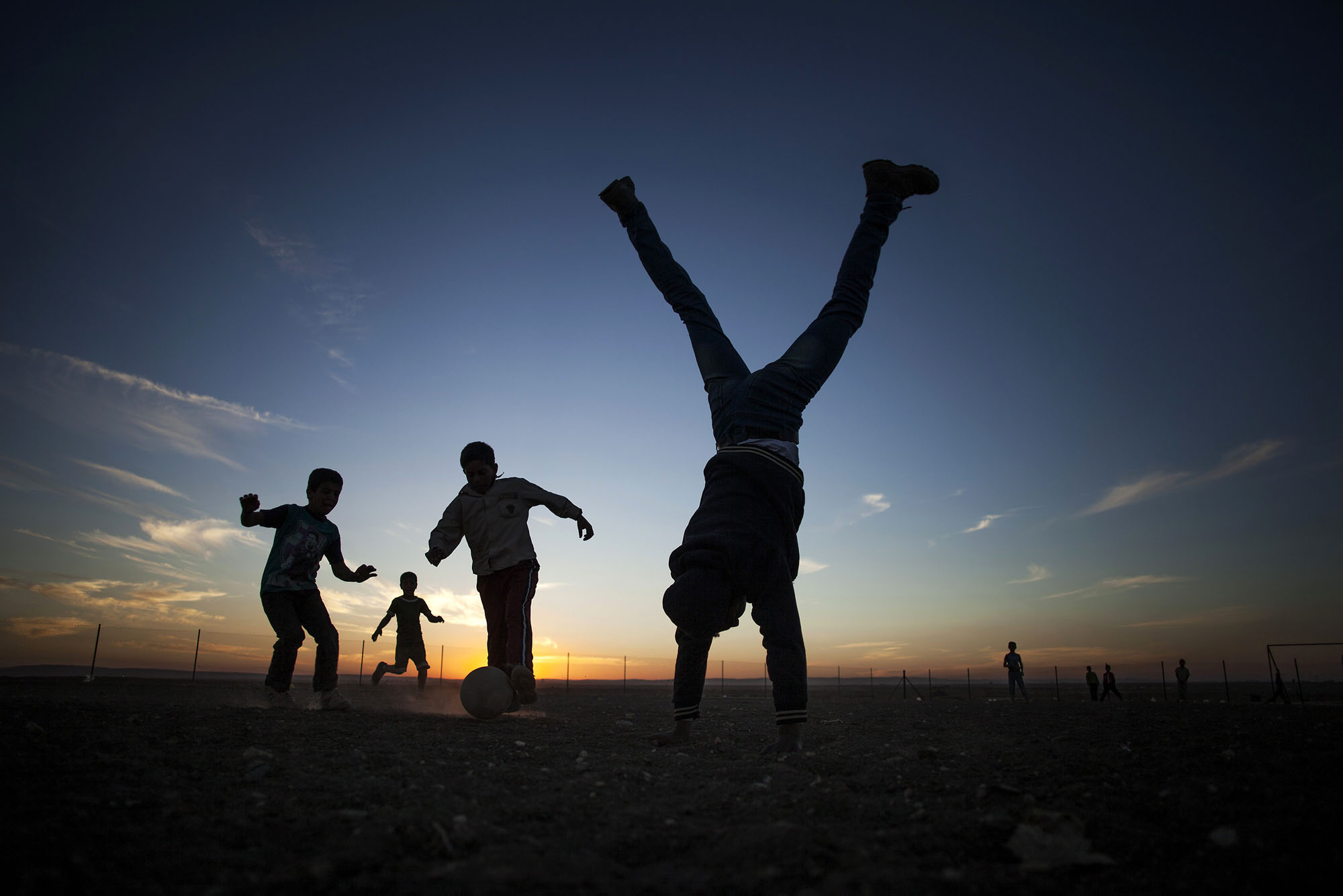 In this Thursday, Oct. 24, 2013, photo, a coach's assistant does a handstand while Syrian children play soccer at the Zaatari refugee camp near the Syrian border in Jordan. With Syria's civil war in its third year, more than 2 million Syrians have fled their country. About 100,000 live in this camp. (AP Photo/Manu Brabo)