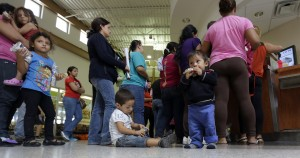 immigrants who entered the U.S. illegally stand in line for tickets at the bus station after they were released from a U.S. Customs and Border Protection processing facility in McAllen, Texas, June 20, 2014. (AP Photo/Eric Gay)