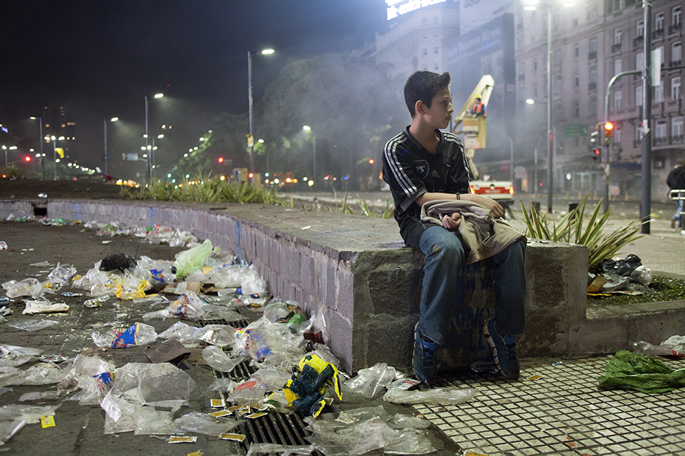 Tear gas settles after a riot at the Obelisco monument in Buenos Aires, Argentina. After the crowd fled, many people were separated from their families. A boy returned to the riot scene and took a seat on the wall at 1 a.m., waiting for his family to find him. (Photo/Brittany Crocker)