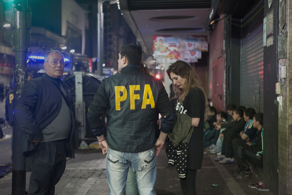 A ywoman pleads with the Argentinean police for her boyfriend, who was detained during a riot in Buenos Aires, Argentina. As police broke the crowd apart with tear gas and rubber bullets, people broke windows, looted shops, and threw rocks at the police. (Photo/Brittany Crocker)