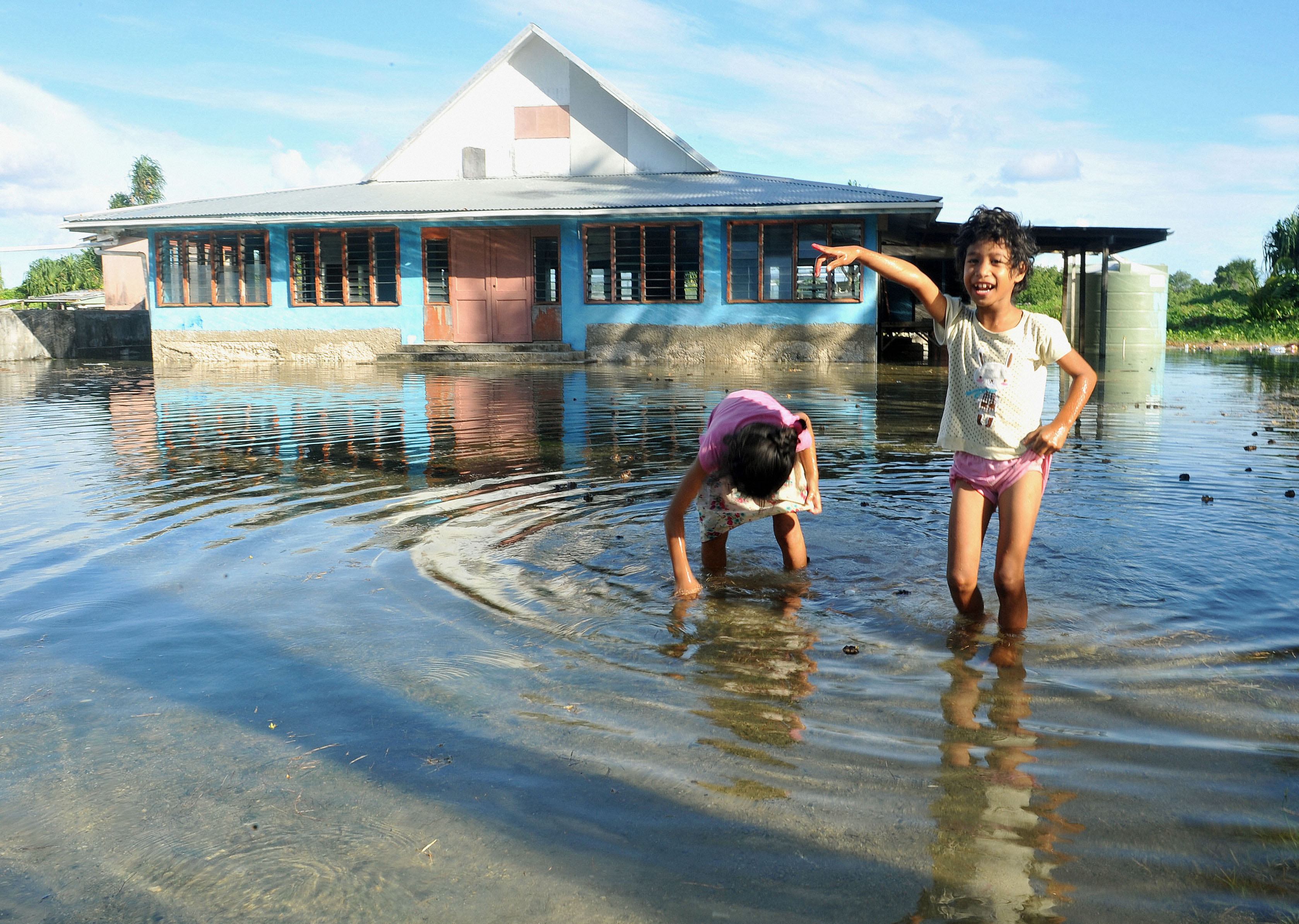FUNAFUTI, Tuvalu - Children play at a plaza flooded with seawater in Funafuti, the capital of Tuvalu, on Jan. 30, 2014. Photo credit: Kyodo / AP Images