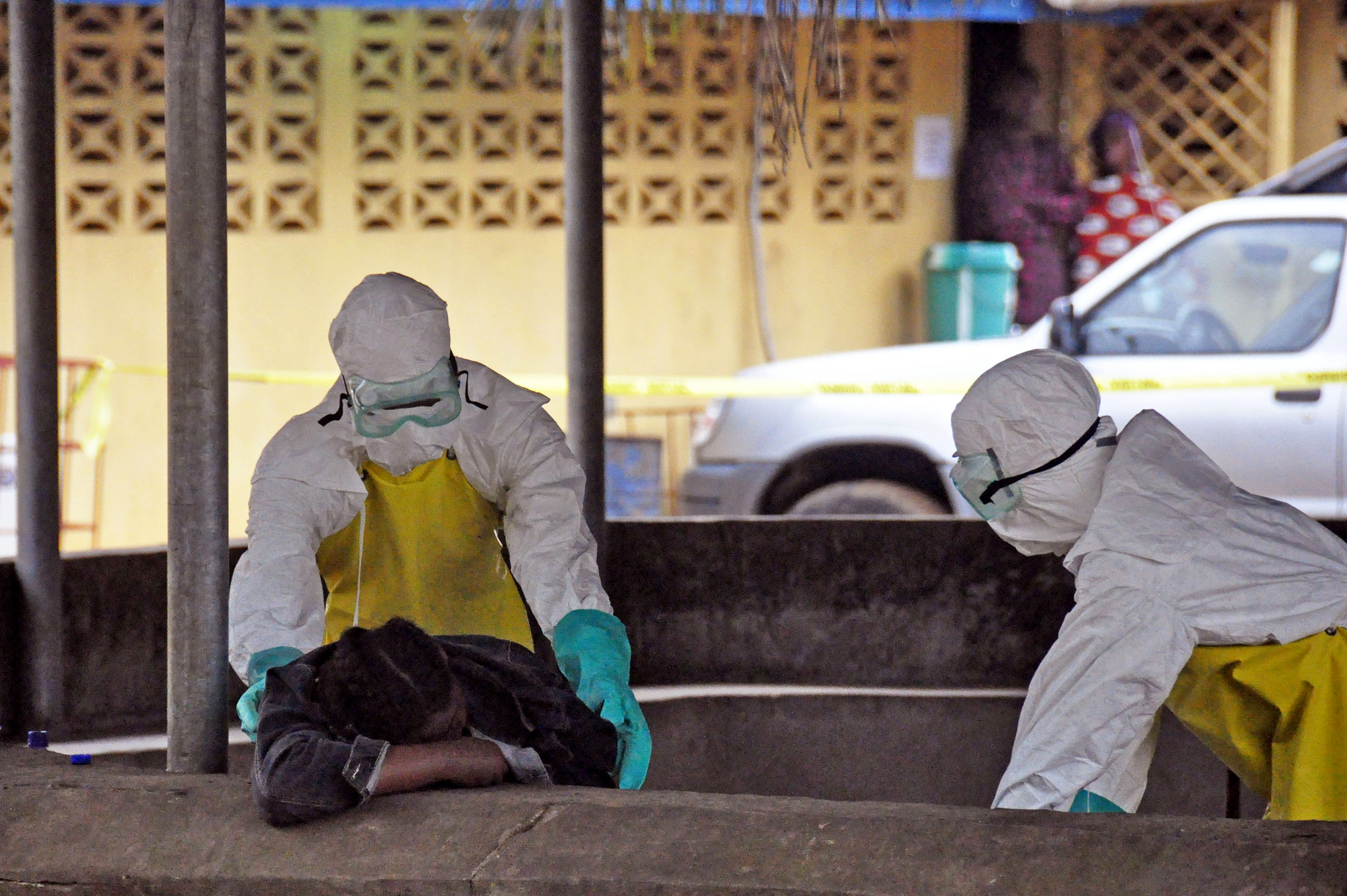 Health workers move the body of a fellow health worker who was found dead in a seat, and who they believe passed away from the Ebola virus, at one of the largest hospitals in the city of Monrovia, Liberia, Saturday, Aug. 16, 2014. Photo credit: AP Photo/Abbas Dulleh