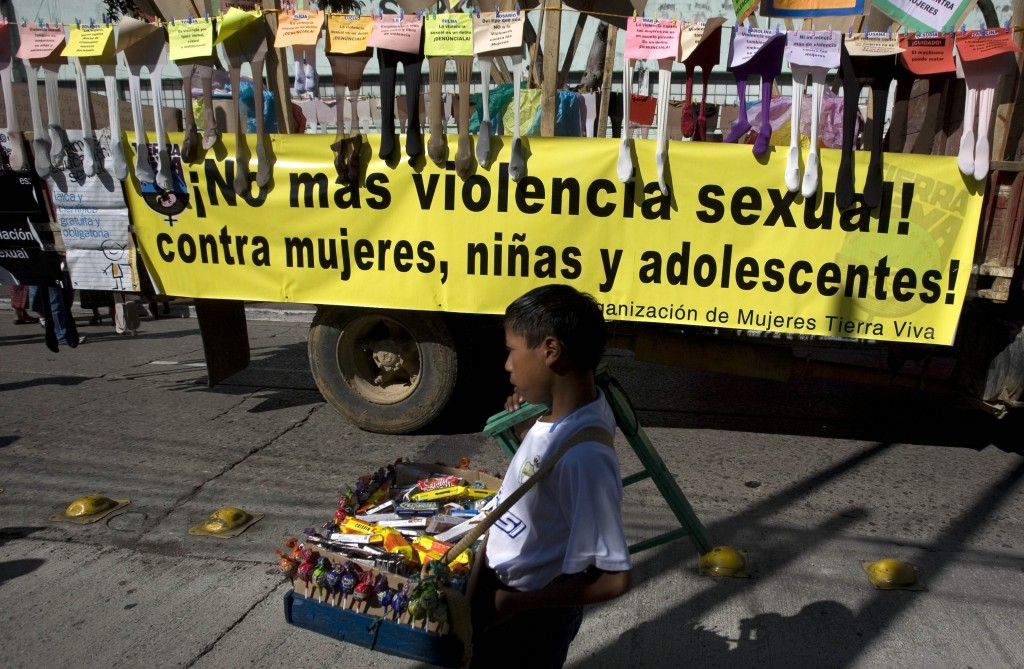 "A street vendor walks next to a banner that reads in Spanish: ""No more sexual violence against women, girls and teenagers"", during the International Day for the Elimination of Violence against Women in Guatemala City,  Nov. 25, 2009. (AP Photo/Moises Castillo)"