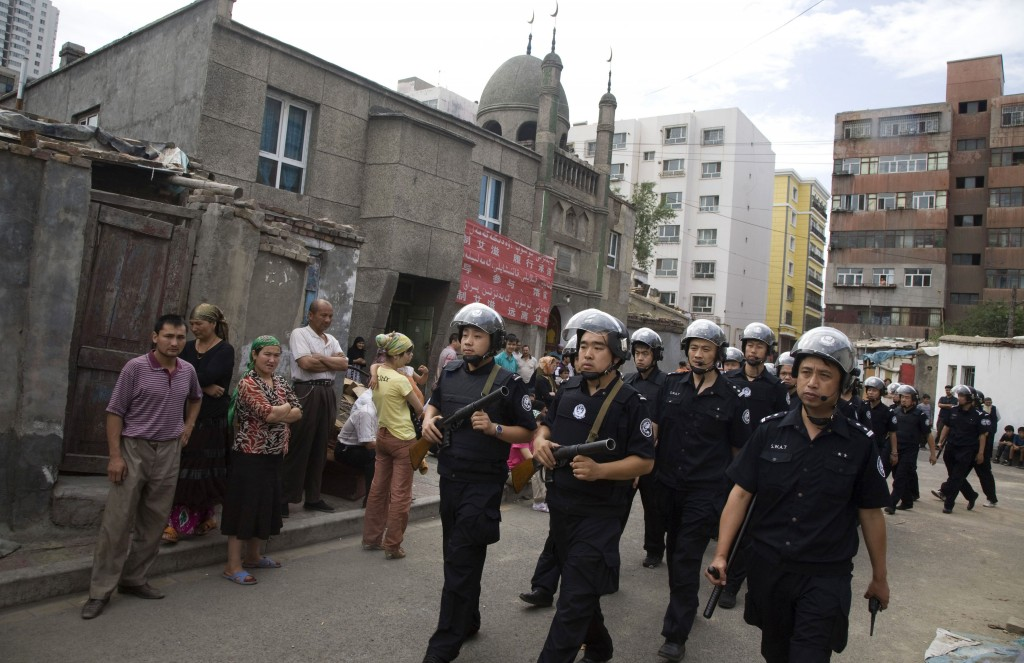 Heavily armed Chinese police officers patrol near a mosque in a Uighur neighborhood a day after Han Chinese mob's attack in Urumqi, China, July 8, 2009. (AP Photo/Ng Han Guan)