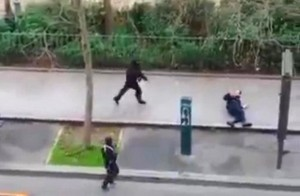 Masked gunman run towards a victim of their gun fire  outside the  French satirical newspaper Charlie Hebdo's office, in Paris, Jan. 7, 2015. (AP Photo)