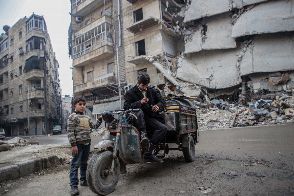 A Syrian man and a child selling oil on the streets of Aleppo, Dec. 2, 2014. (Ibrahim Khader)