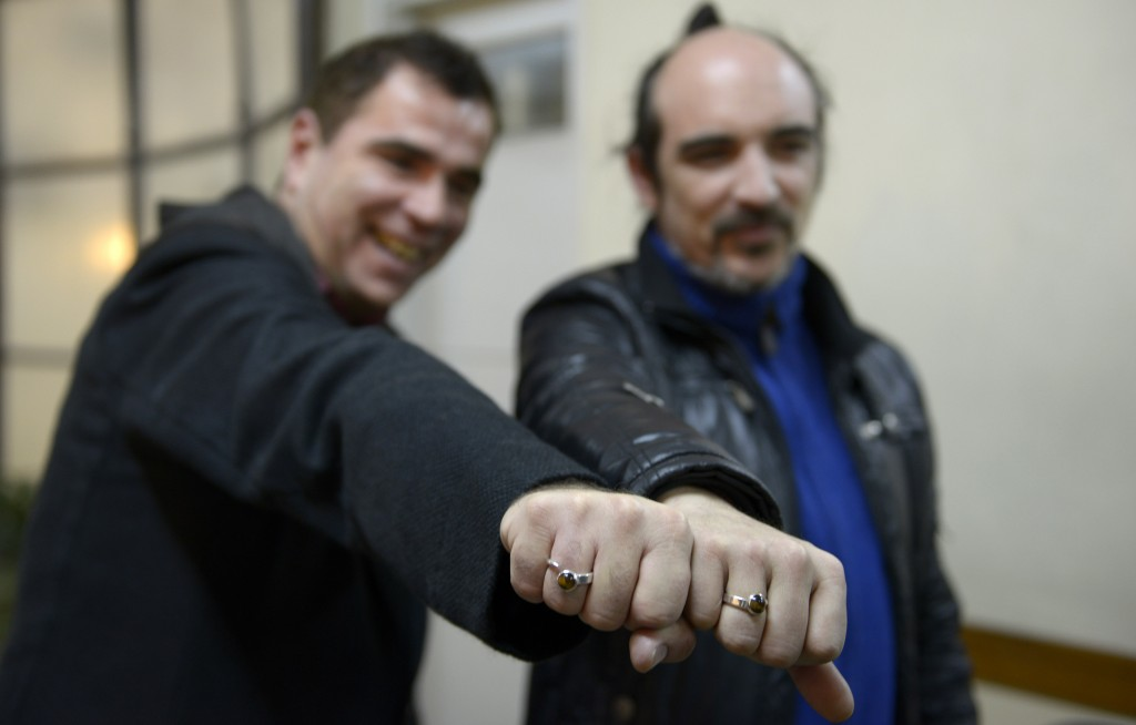 Rodrigo Borda, right, and his partner Sergio Miranda show off their engagement rings after signing up to marry at the the Civil Registry office in Montevideo, Uruguay,  Aug. 5, 2013. (AP Photo/Matilde Campodonico)