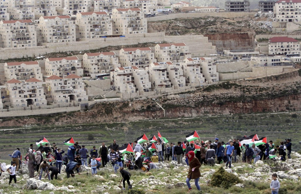 Palestinian protesters carry national flags and plant olive trees facing the Israeli settlement of Beitar Illit during a protest marking Land Day near the West Bank city of Bethlehem,  March 30, 2015. Land Day commemorates riots on March 30, 1976, when six people were killed during a protest by Israeli Arabs whose property was annexed in northern Israel to expand Jewish communities. (AP Photo/Mahmoud Illean)