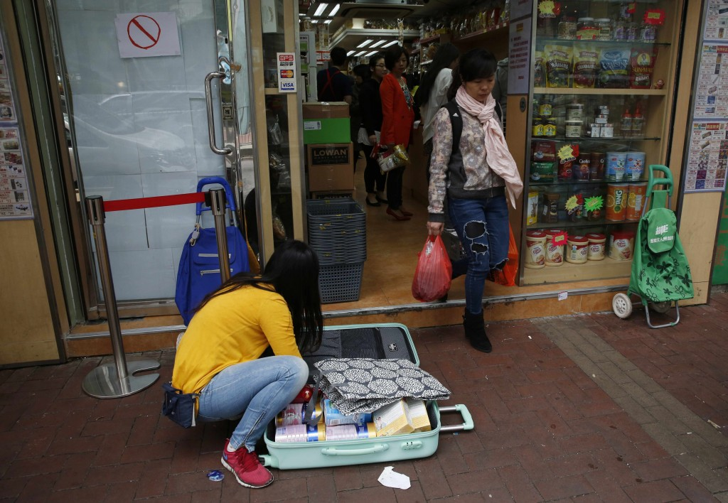 A woman packs goods in front of a shop before taking them to the mainland China, at Sheung Shui district in Hong Kong, April 10, 2015. (AP Photo/Kin Cheung)
