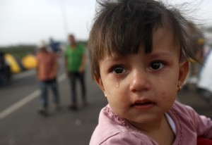 "A girl cries at the ""Horgos 2"" border crossing into Hungary, near Horgos, Serbia, Sept. 17, 2015. (AP Photo/Darko Vojinovic)"