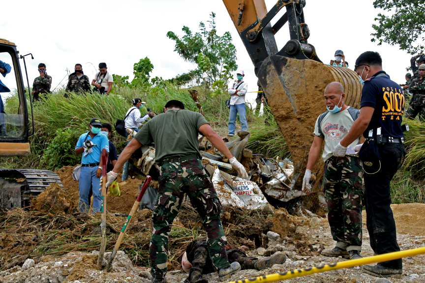 An excavation team works with a backhoe to exhume bodies. (Credit: Nonoy Espina)