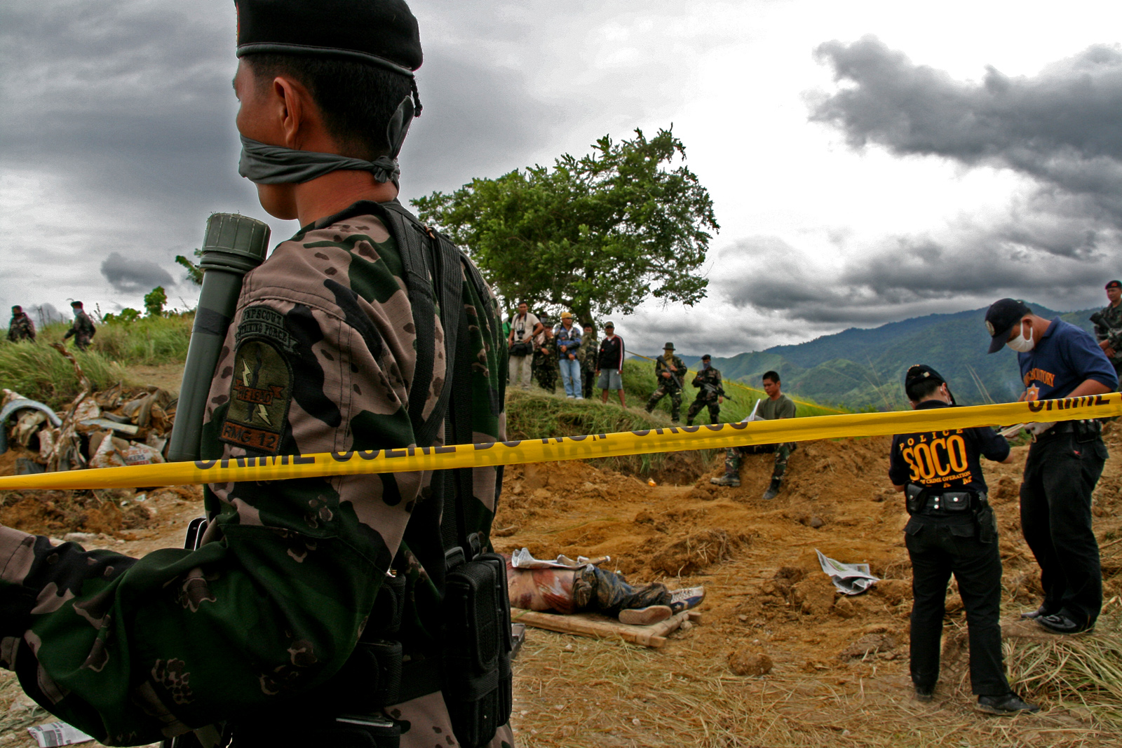 Local police secured the massacre grave and covered his nose with a handkerchief (Credit: Nonoy Espina)