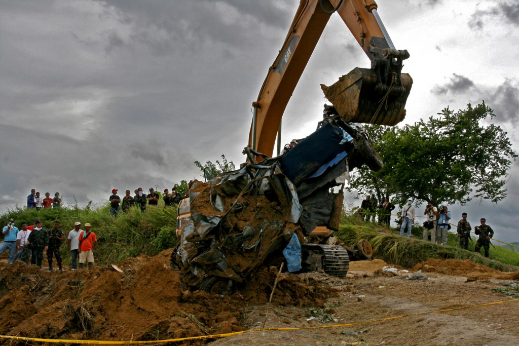 A backhoe lifts a vehicle from a grave days after the massacre (Nonoy Espina)