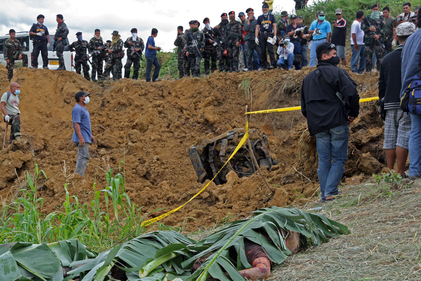 Police cordoned off the grave. Armed Philippine military were standing up the hill. Excavation team lined up the bodies and covered them with banana leaves (Credit: Nonoy Espina)