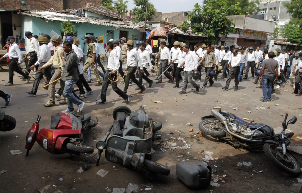 Indian policemen in plain clothes walk past vehicles damaged during a clash between two groups in Ahmedabad, India, Aug. 25, 2015. (AP Photo/Ajit Solanki)