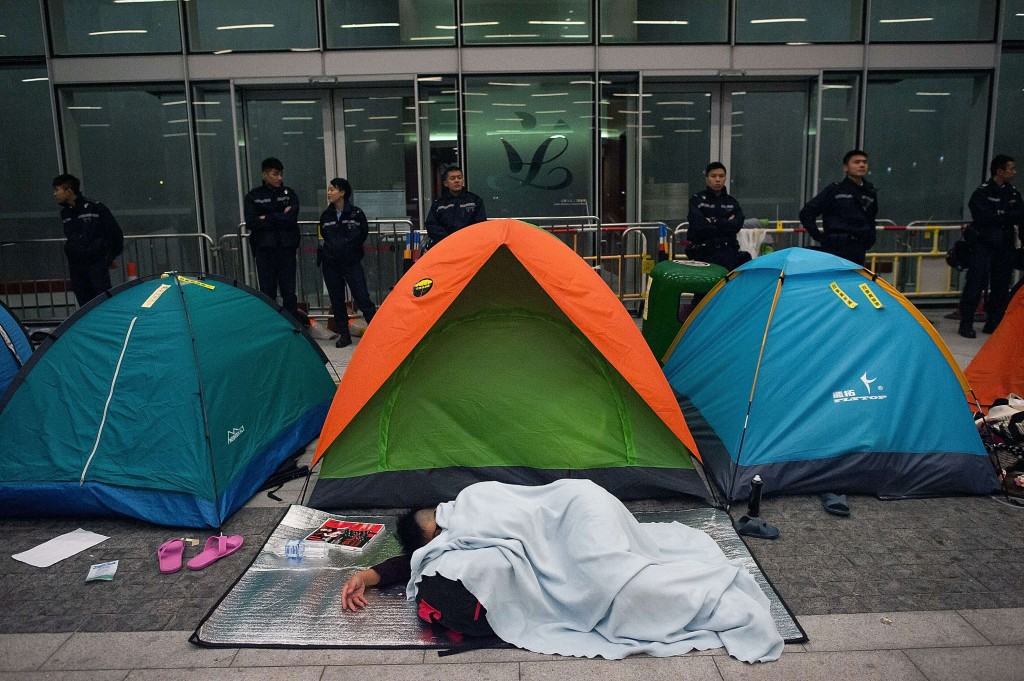 A pro-democracy protester sleeps on the floor outside the Legislative Council building entrance after clashes with police on November 19, 2014 in Hong Kong.