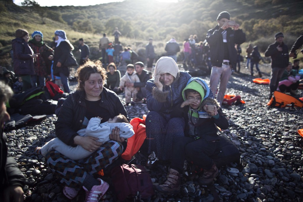 A Yazidi refugee family from Iraq cries while resting on the seashore shortly after arriving on  a vessel in Lesbos, Nov. 26, 2015.  (AP Photo/Muhammed Muheisen)