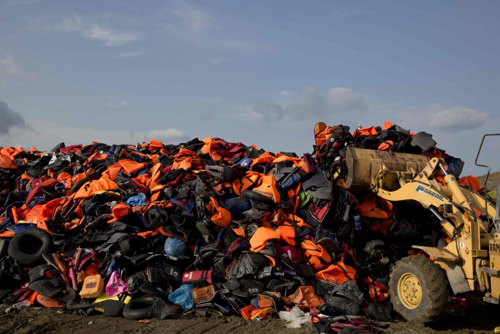 An excavator works on a huge pile of life vests and dinghies at a local dump of the island of Lesbos, Sept. 24, 2015. (AP Photo/Petros Giannakouris)