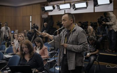 Catalin Tolontan at a mic, asking a question during a press conference.