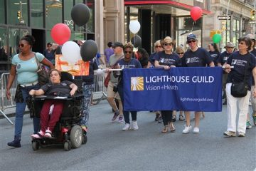 Marchers, including one in a wheelchair and several carrying a banner for the Lighthouse Guild, parading down a city street with balloons.
