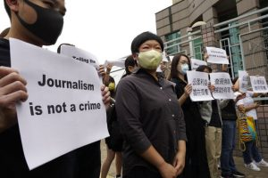 "Chy Yuk-ling, wearing a mask against COVID, stands with similar masked supporters who are carrying signs reading ""Journalism is not a crime."""