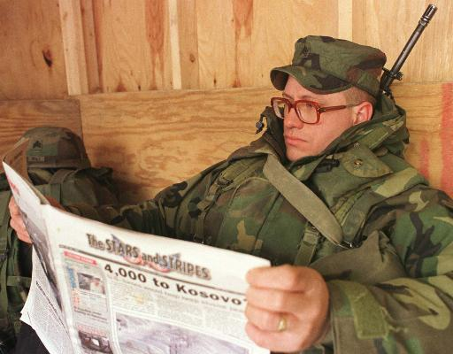 Uniformed soldier with rifle reading Stars and Stripes newspaper