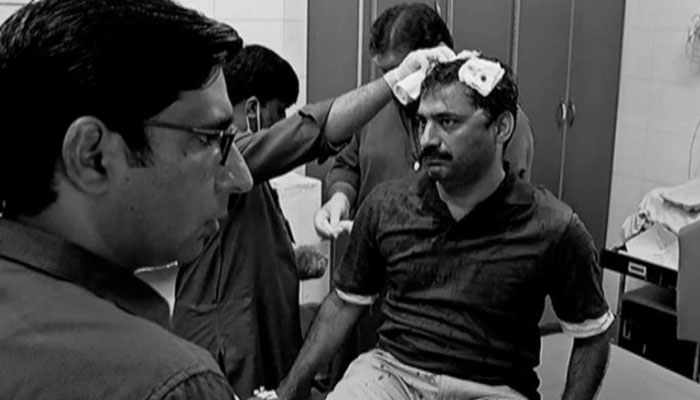 Black and white photo of Ahmad Noorani in hospital with bloody bandages on his head.