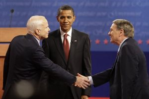 Then-Sen. Barack Obama looks on as moderator Jim Lehrer shakes hands with Sen. John McCain on a stage in Oxford, Mississippi after Obama and McCain held their first presidential debate.