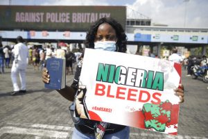 "Masked woman at a protest carrying a green and white sign that reads ""Nigeria Bleeds."" The word ""Bleeds"" is in red."