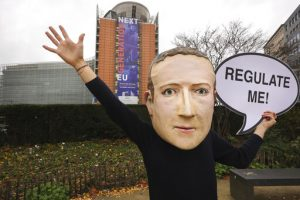 """Person wearing Mark Zuckerberg mask and waves with one hand and holds sign reading """"regulate me"""" in the other."""
